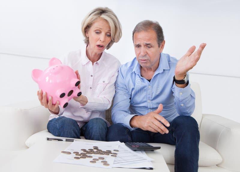 拿着piggybank的震惊夫妇 免版税库存图片