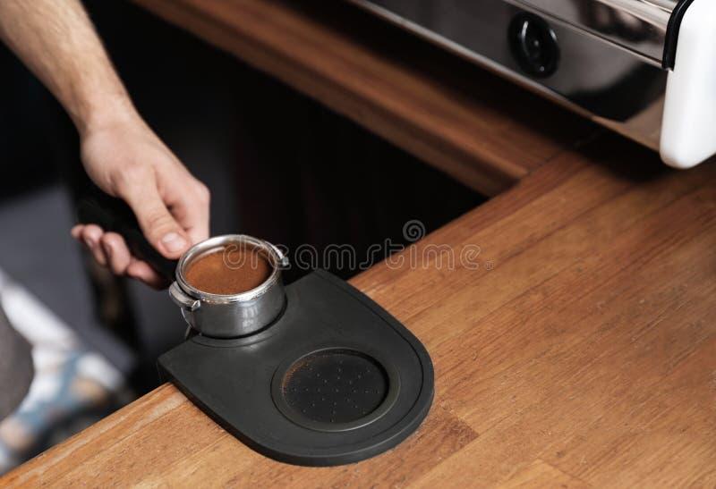 拿着portafilter用被碾碎的咖啡的Barista砸紧席子在酒吧柜台,特写镜头 库存照片