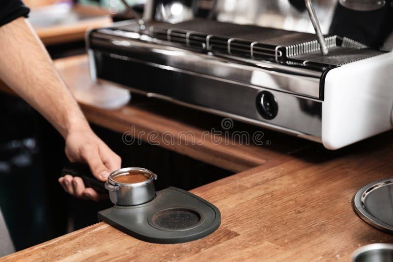 拿着portafilter用被碾碎的咖啡的Barista砸紧席子在酒吧柜台,特写镜头 图库摄影