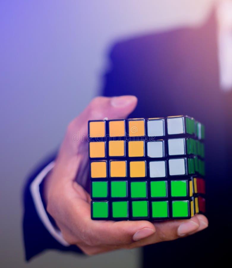 拿着Rubik的立方体的商人 免版税库存照片