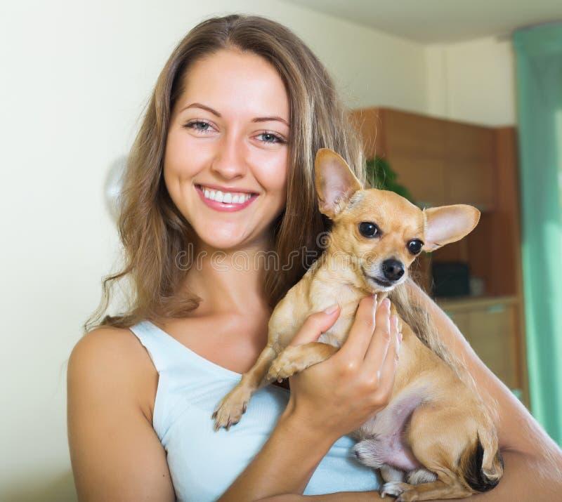 拿着Russkiy玩具狗的愉快的女孩 免版税库存照片