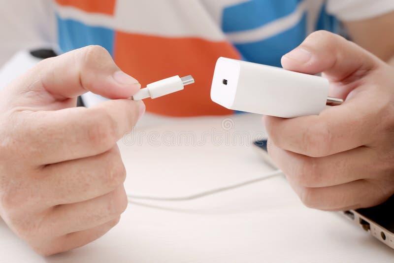 拿着USB缆绳和适配器的人 免版税图库摄影