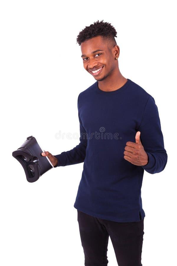 拿着vr虚拟现实耳机ov的非裔美国人的年轻人 免版税库存照片