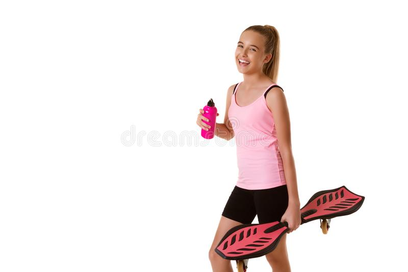 拿着waveboard和瓶水的快乐的运动的青少年的女孩 免版税库存照片