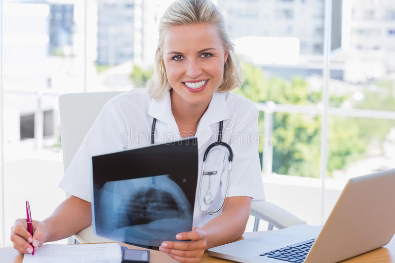 拿着x光芒的快乐的护士在她的办公室 库存照片