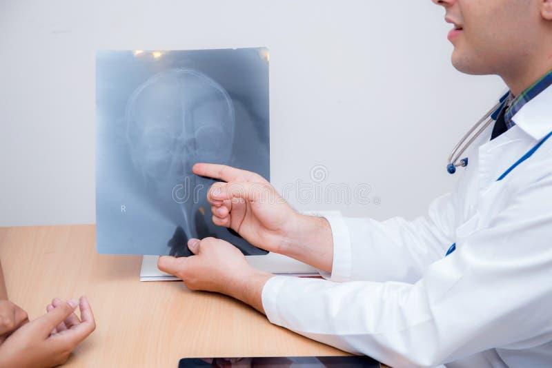拿着X-射线的亚裔人医生谈论妇女耐心 免版税库存图片