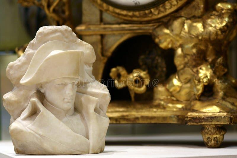 拿破仑・波拿巴胸象,金古色古香的时钟背景 图库摄影