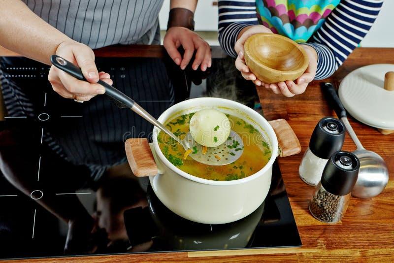 拿走与钢特纳的妇女的手一棵煮沸的葱 在黑火炉的被打开的白色平底深锅 烹调鸡汤面 库存图片