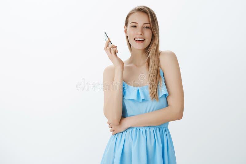 拿走智能手机的女孩作为人群的,中断的交谈seing的朋友通过手机聊天微笑逗人喜爱在 免版税库存照片