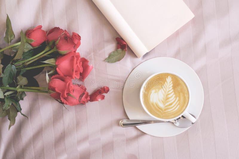 拿铁咖啡玫瑰开花和在床上的空的书 图库摄影