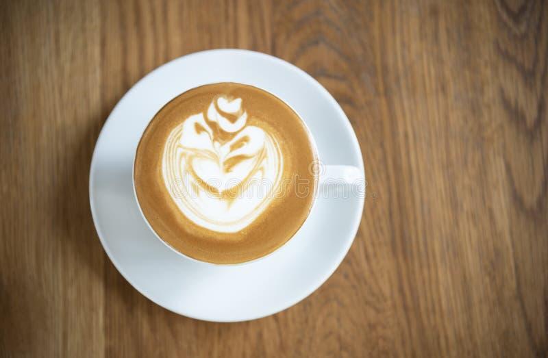 拿铁或热奶咖啡与泡沫的泡沫,咖啡杯顶视图在木桌上在咖啡馆 免版税库存照片