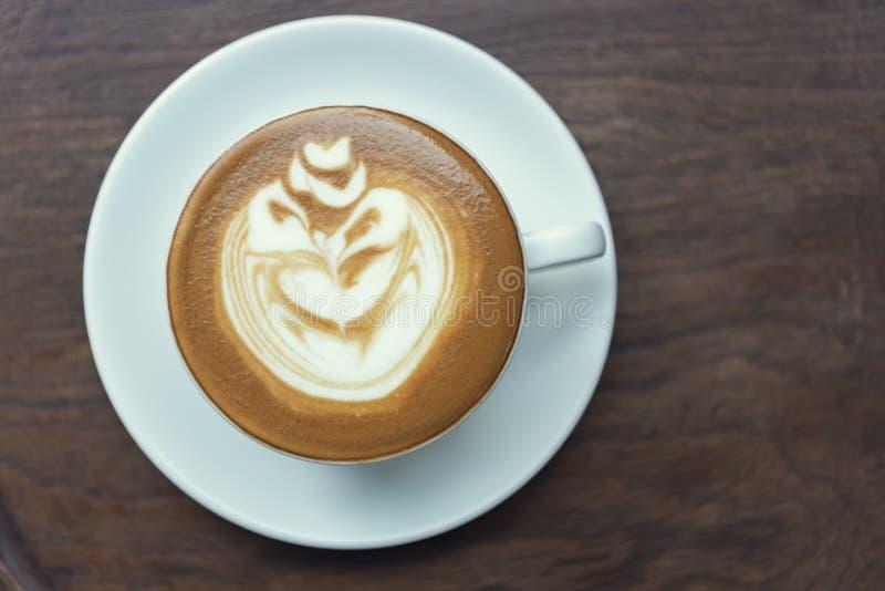 拿铁或热奶咖啡与泡沫的泡沫,咖啡杯顶视图在桌上在咖啡馆 免版税图库摄影