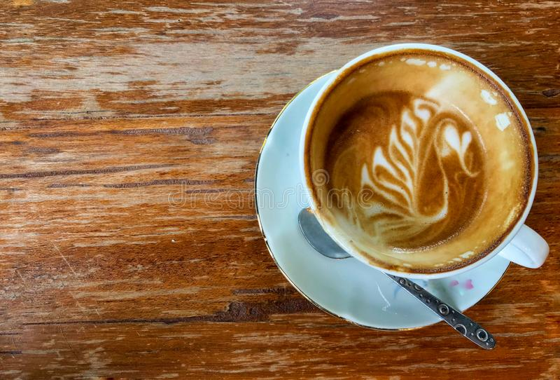拿铁艺术咖啡保持白色杯子的一半有在木桌上把放的匙子的和coppy spaceได้ 免版税库存照片