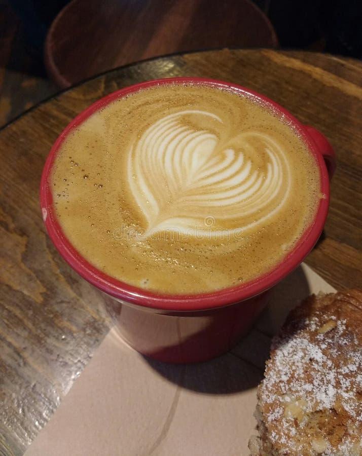 拿铁艺术心脏,早晨咖啡用一个杏仁新月形面包用搽粉的糖 免版税库存照片
