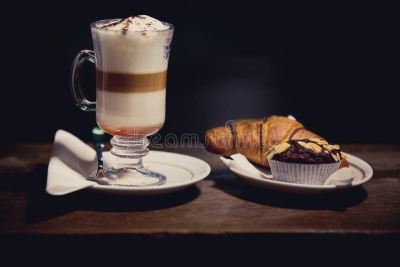 拿铁macchiato玻璃与富有的牛奶泡沫的 热巧克力和咖啡饮料用被鞭打的奶油色和甜杯形蛋糕和新月形面包 图库摄影