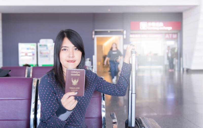 持与行李,等待的飞行的妇女护照在机场 免版税库存照片