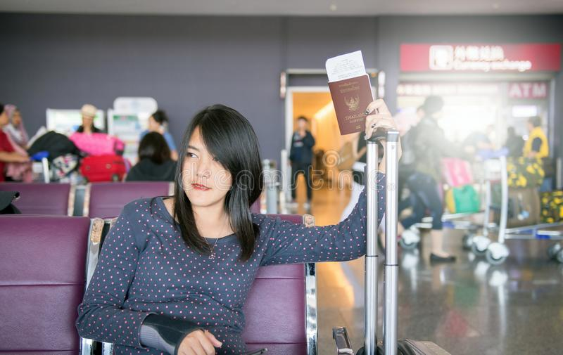 持与行李,等待的飞行的妇女护照 库存图片