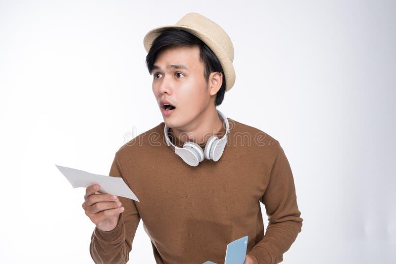 持在灰色backgro的愉快的年轻旅游亚裔人护照 库存照片
