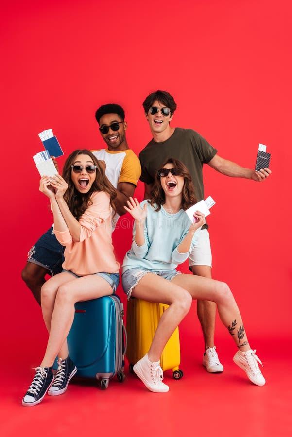 持护照的全长小组愉快的激动的朋友 免版税图库摄影