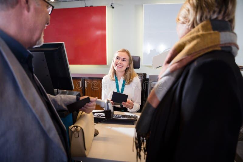 持护照的职员,当看资深夫妇在机场时 库存图片