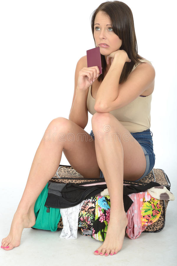 持护照的紧张的急切少妇坐一个溢出的手提箱 免版税库存照片
