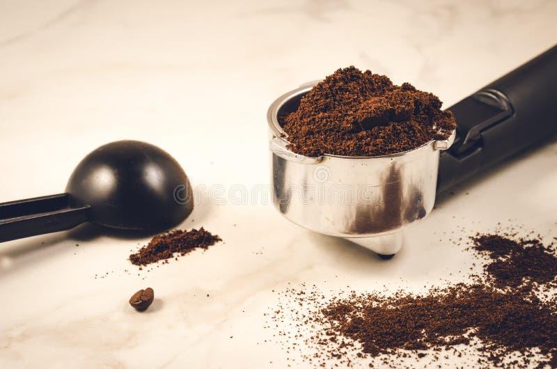 持有人充满碾碎的咖啡一个黑匙子/持有人充满碾碎的咖啡在大理石背景的一把黑匙子 r 库存图片