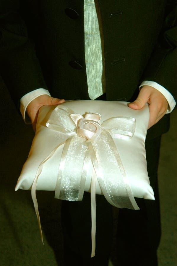 持票人举行枕头环形婚礼 免版税图库摄影
