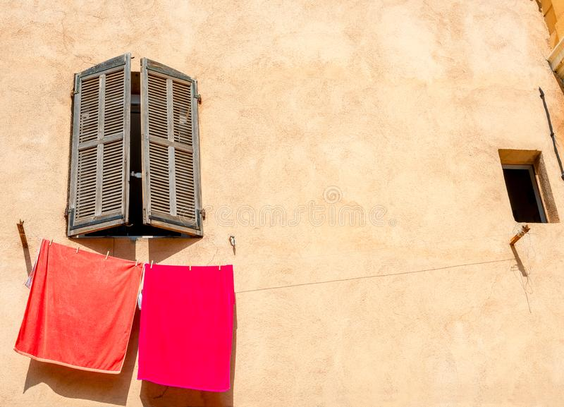 挂在带窗户的黄色房屋墙壁上的红色毛巾 免版税库存图片