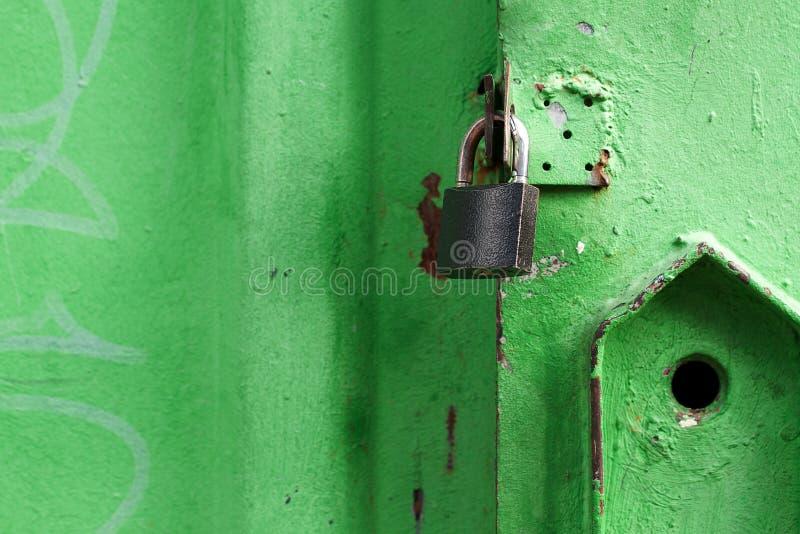 挂锁关闭的破旧的绿色门 库存图片