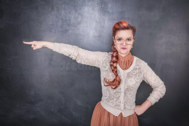 指出在黑板背景的严肃的妇女老师 免版税库存图片