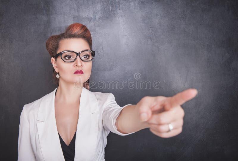 指出在黑板背景的严肃的老师 库存照片