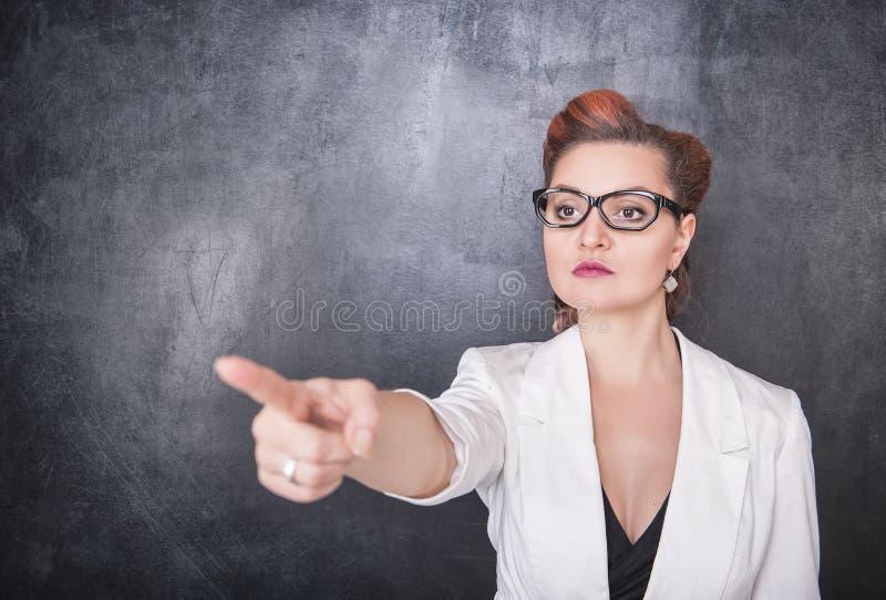 指出在黑板背景的严肃的老师 免版税库存照片