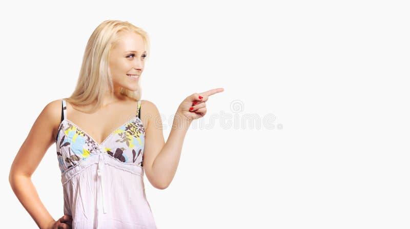 指向一个空的广告空间的白肤金发的妇女 免版税库存图片
