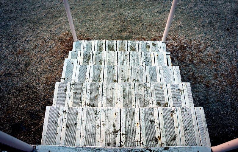 指向下来地面的残破的离开的木台阶 库存照片