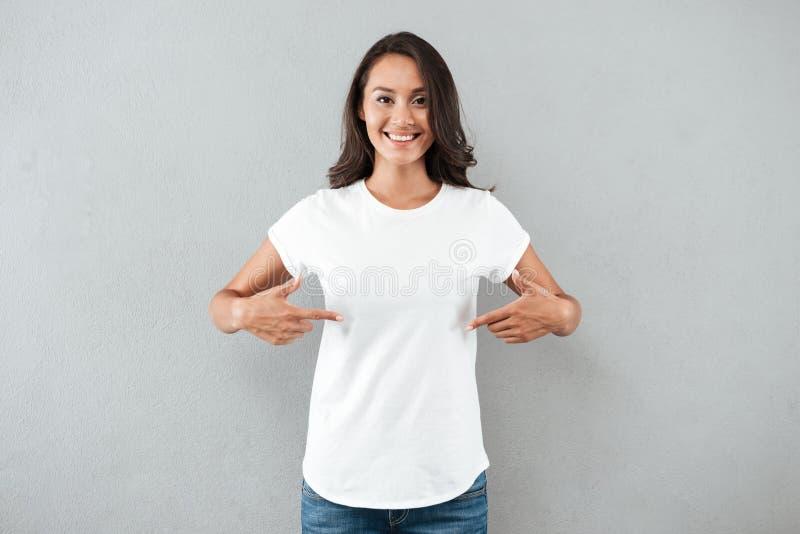指向与两个手指的愉快的微笑的亚裔妇女 免版税库存图片
