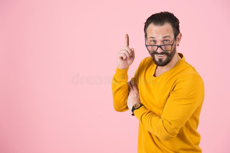 指向与在鼻子的玻璃的有胡子的时尚人 人在粉红彩笔背景的演播室有想法被隔绝 库存图片