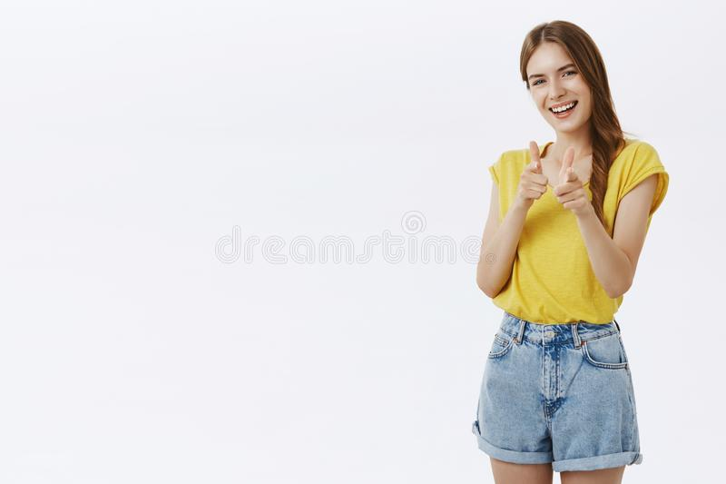 指向与手指枪的友好吸引人妇女打手势在照相机和微笑快乐,好象招呼最好 免版税库存照片
