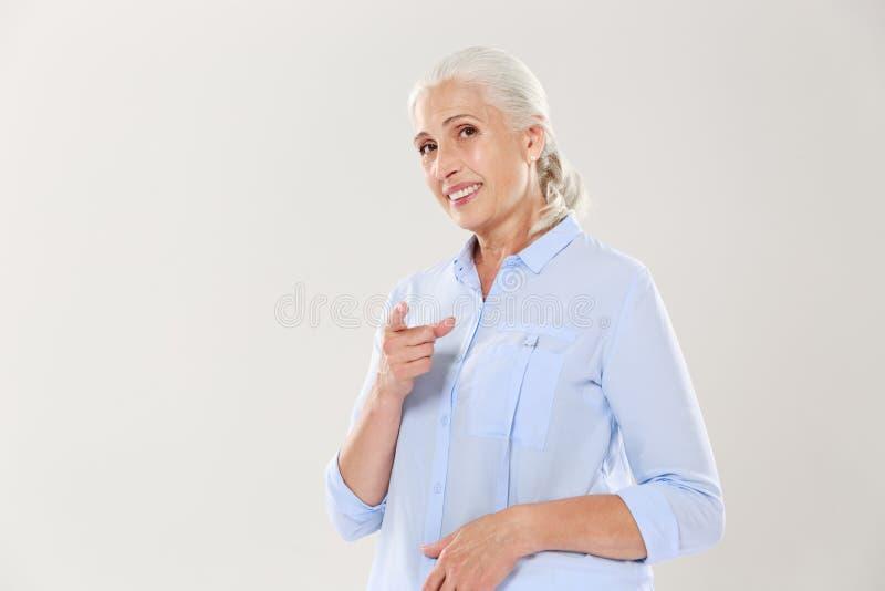指向与手指的微笑的老妇人画象您 免版税图库摄影