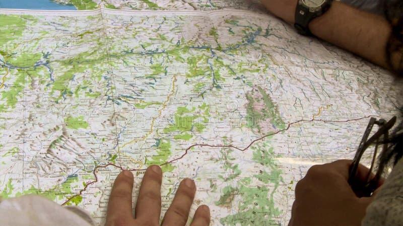 指向世界地图的地方的接近的观点的男人和妇女 库存图片