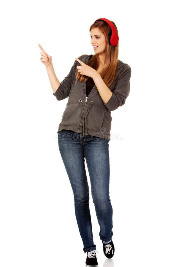 指向为某事的愉快的少年妇女 库存照片