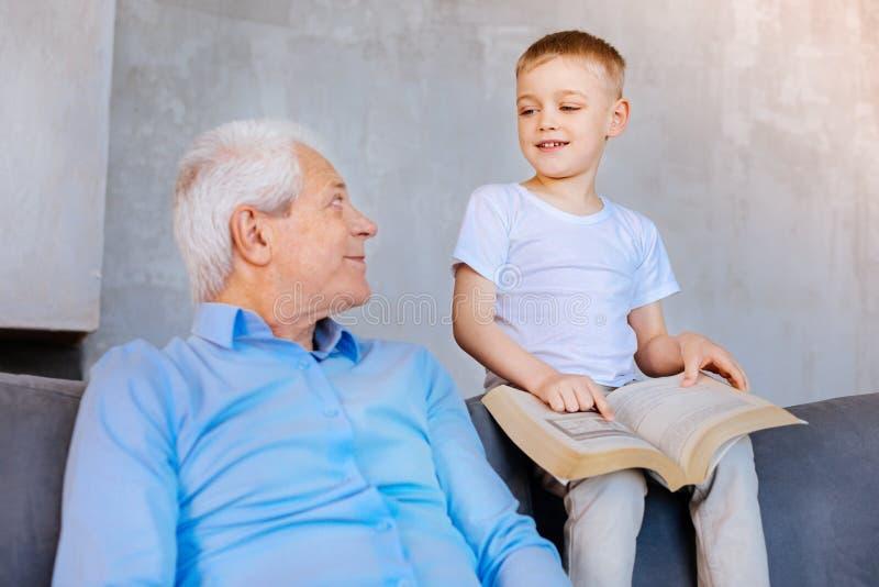 指向书页的快乐的聪明的男孩 库存照片