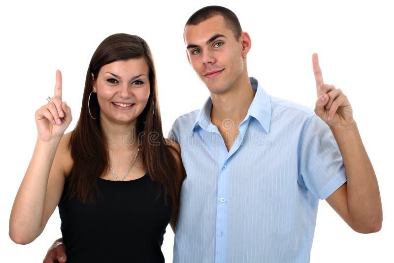 指向他们的年轻人的夫妇高兴手指 免版税库存图片