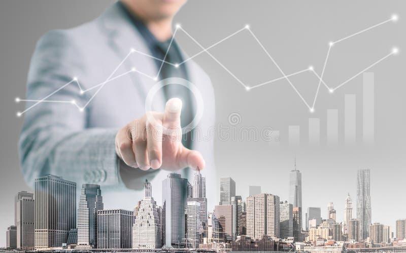 指向他的手指的商人和接触有大厦前景和财政信息图表的屏幕 免版税库存照片
