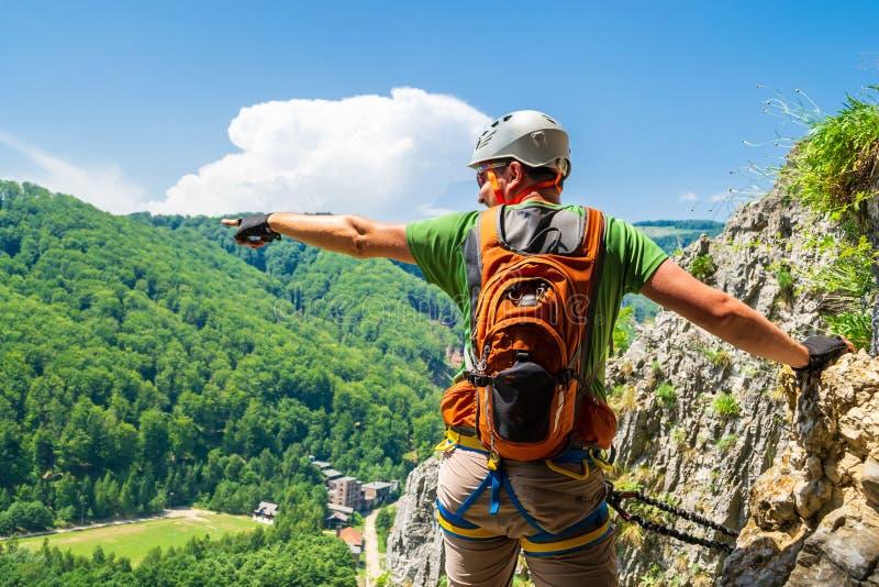 指向他的手的旅游登山人入在a的距离通过ferrata路线在巴亚de非夏尔,戈尔日县,罗马尼亚 免版税库存照片