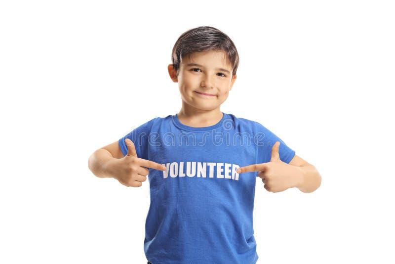 指向他的蓝色T恤杉的儿童志愿者 免版税库存照片