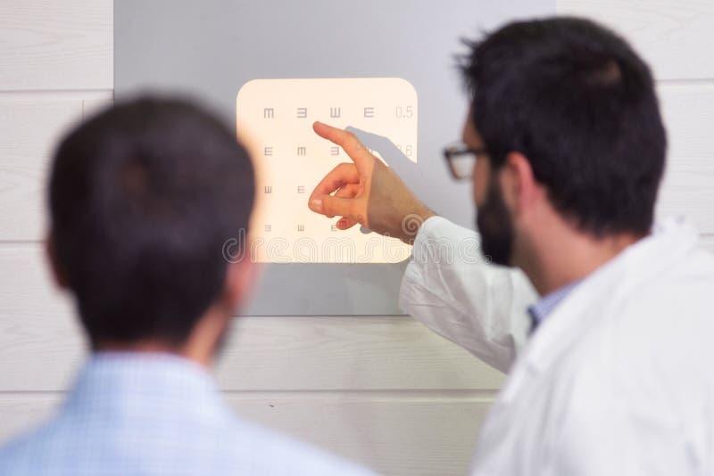 指向信件的眼科医生,当患者读视力检查表时 免版税库存照片