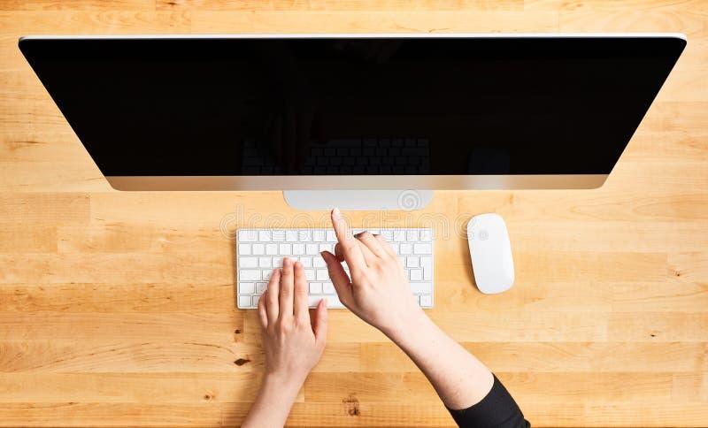 指向台式电脑的女性手 免版税图库摄影