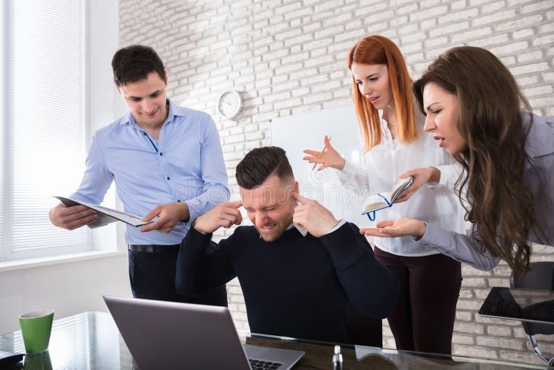 指向同事的恼怒的商人 库存图片