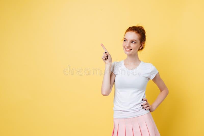 指向和握在臀部的无忧无虑的姜女孩胳膊 免版税库存照片