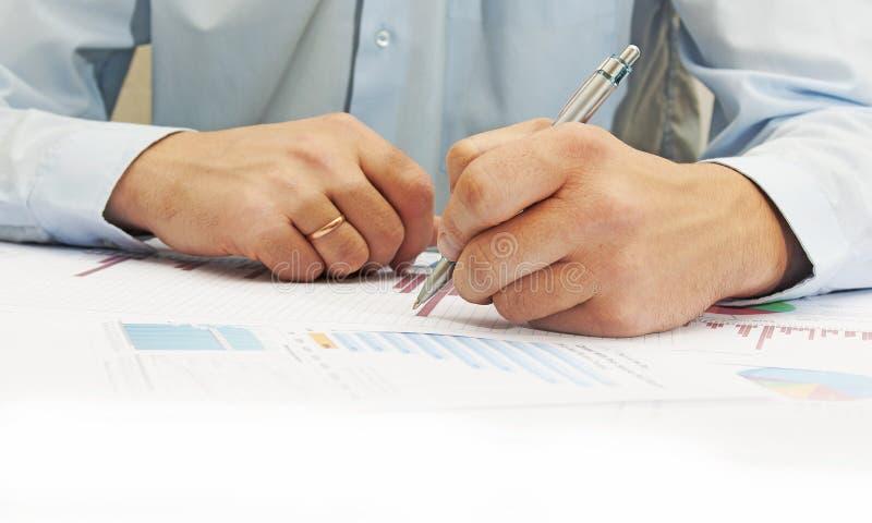 指向商业文件的男性手的图象在讨论时在会议上 免版税库存照片